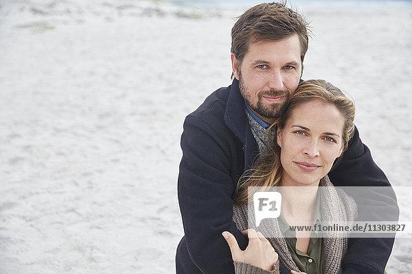 Portrait serene affectionate couple hugging on beach