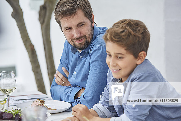 Father and son eating lunch at patio table