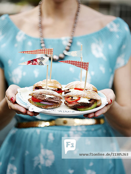 Woman holding plate with sandwiches