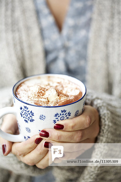 Womans hands holding mug with hot chocolate