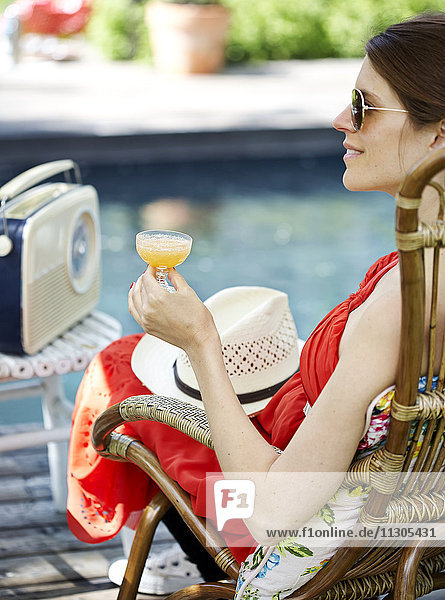 Woman with cocktail at swimming pool