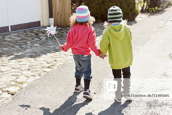Two girls walking and holding hands