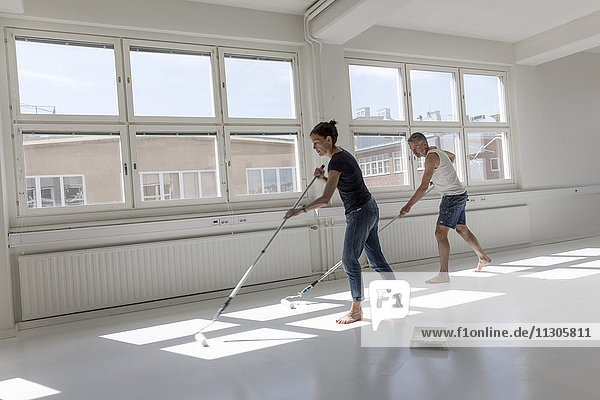 Man and woman painting floor