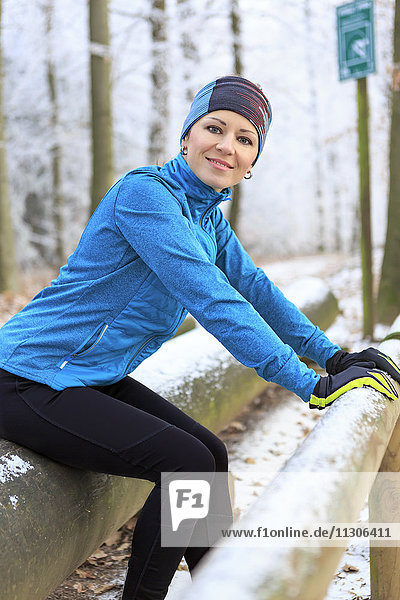 Woman training on fitness trail in winter forest
