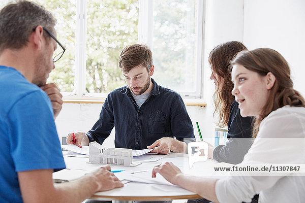 Ein modernes Büro. Zwei Männer und zwei Frauen sitzen bei einer Sitzung an einem mit Plänen und Papieren gedeckten Tisch.