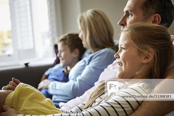 Eine Familie zu Hause. Zwei Erwachsene und zwei Kinder  die zusammen auf einem Sofa sitzen.