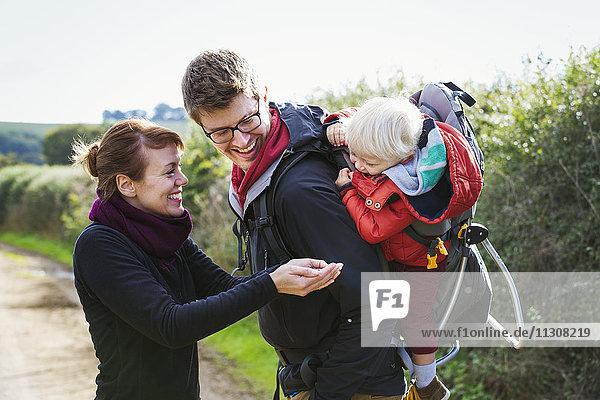 Eltern und ein Kind auf einem Landspaziergang  ein Junge im Rucksack.