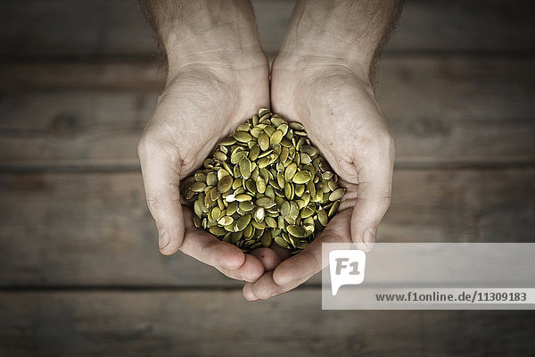Pumpkin seeds in mans hands  close-up
