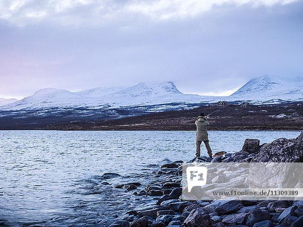 Man fishing at dusk
