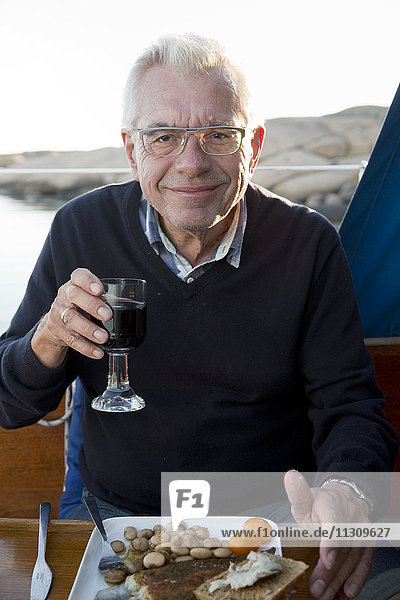 Smiling man having meal on boat