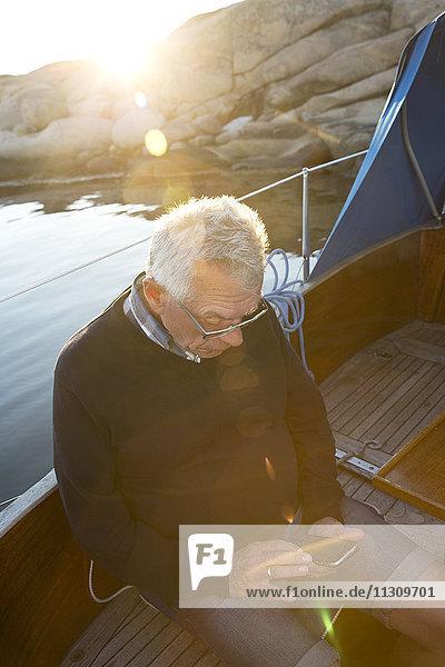Senior man on boat using cell phone