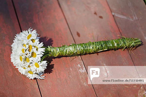 Daisy bouquet on wooden floor