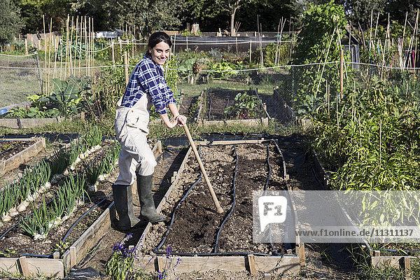 Frau arbeitet auf dem Bauernhof  bereitet Gemüsebeet mit Hacke zu