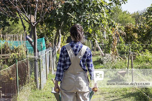 Frau bei der Arbeit auf dem Bauernhof schiebt Schubkarre