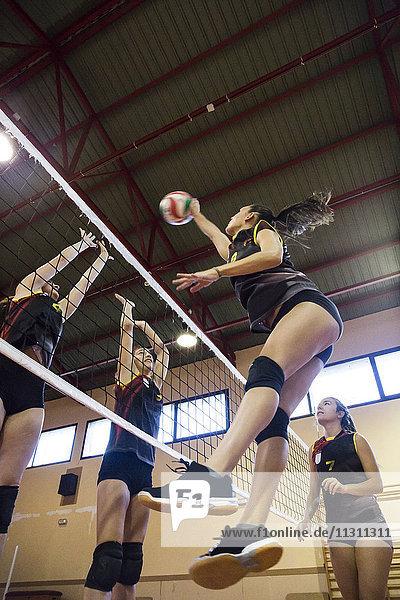 Volleyballspieler  der den Ball während eines Volleyballspiels aufspießt.