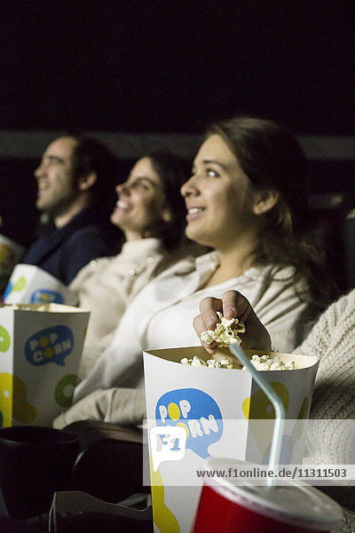 People watching a movie in a cinema and eating pop corn