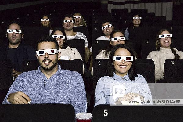 Leute mit 3D-Gläsern  die sich einen Film im Kino anschauen.