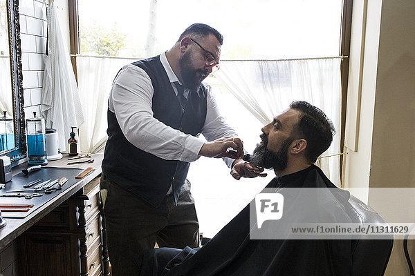 Barbier bürstet den Bart eines Mannes mit einer Haarbürste