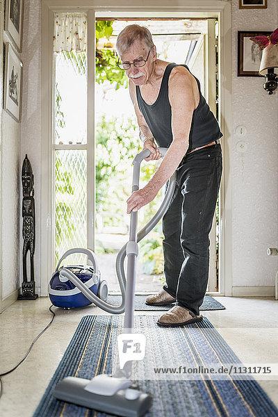 Senior man vacuuming at home