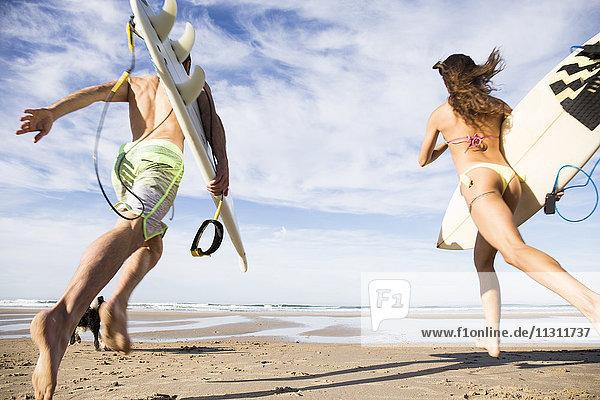 Paar mit Surfbrettern am Strand
