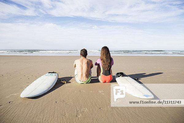 Paar mit Surfbrettern am Strand sitzend