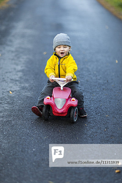 Boy on toy car in road