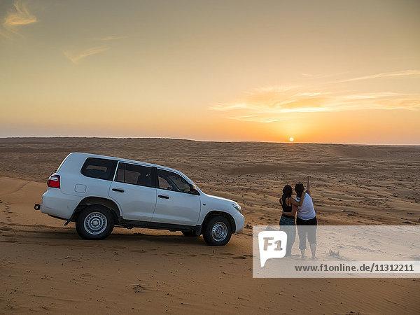 Oman  Al Raka  zwei junge Frauen stehen neben einem Geländewagen auf einer Wüstendüne und beobachten den Sonnenuntergang.