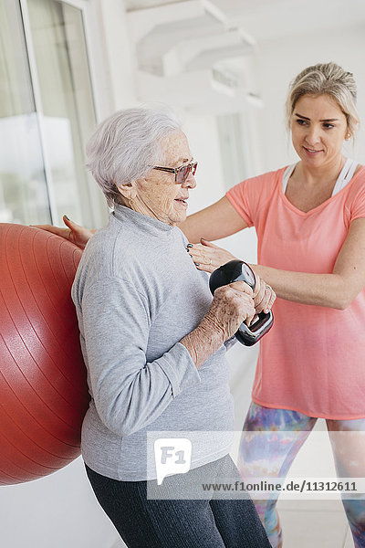 Senior woman exercising with fitness instructor