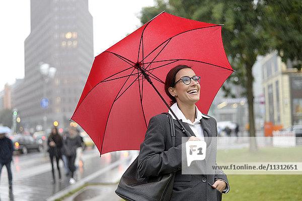 Deutschland  Berlin  glückliche Geschäftsfrau mit rotem Schirm am Potsdamer Platz