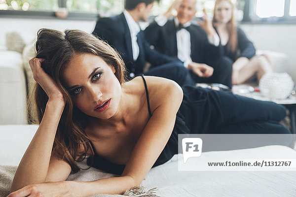 Beautiful woman lying on couch  party guests in background