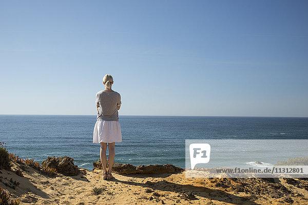 Frau steht an der Küste und schaut in die Ferne.