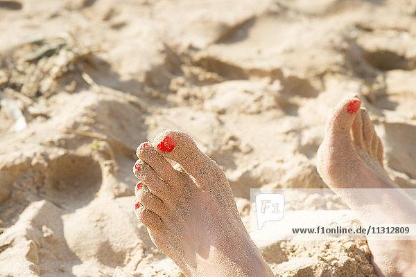 Füße mit rotem Nagellack in Sand