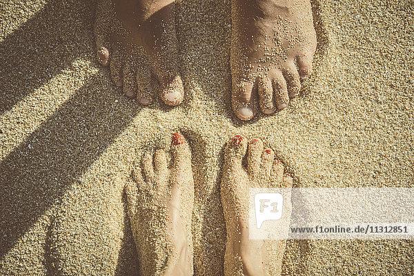 Füße eines im Sand stehenden Paares von oben gesehen