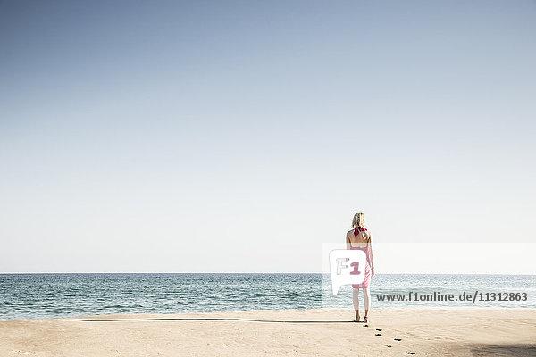 Rückansicht der am Strand spazierenden Frau