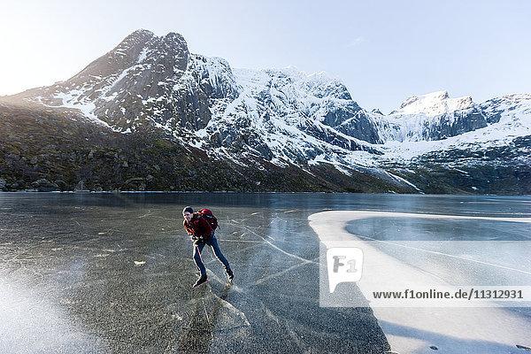 Man ice-skating on frozen lake