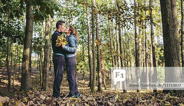 Pärchenküssen im Herbstwald