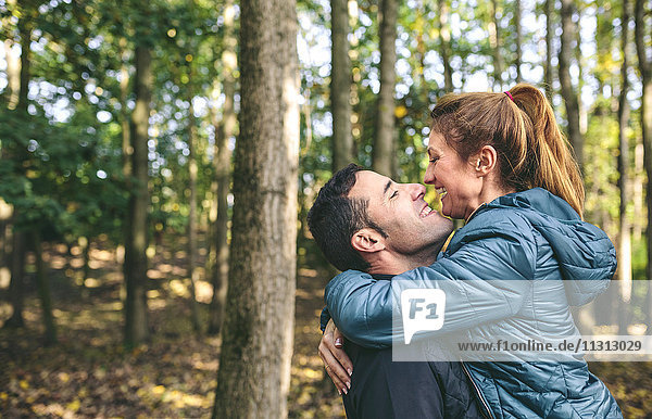 Glückliches Paar von Angesicht zu Angesicht im Herbstwald