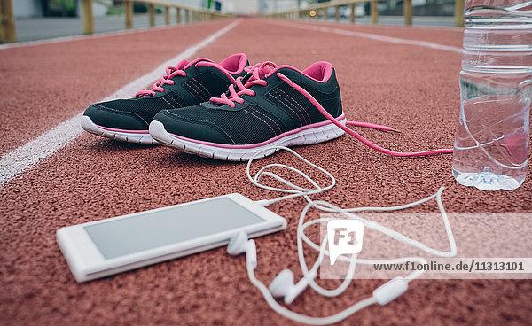 Sportschuhe  Smartphone mit Ohrstöpseln und Wasserflasche auf Tartanbahn