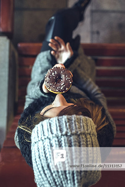 Woman sitting on bench eating doughnut with chocolate icing  top view