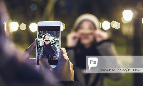 Man taking picture of his girlfriend pouting mouth