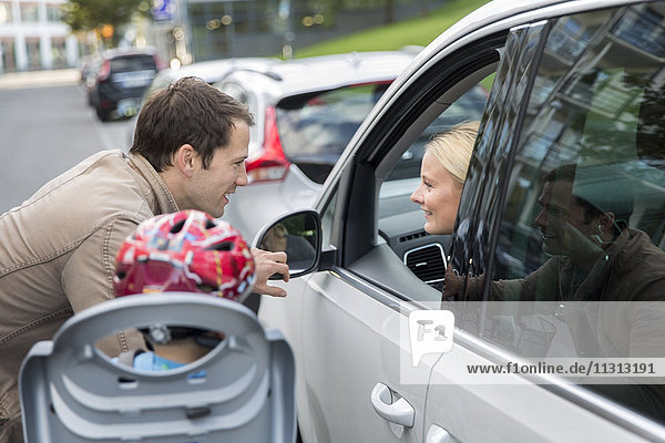 Man talking to woman while she is driving car