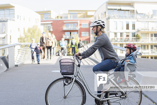 Woman riding bicycle with son sitting in back seat