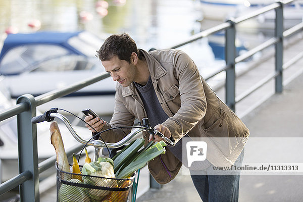 Man leaning at his bicycle and texting on mobile phone