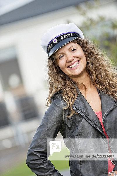 Portrait of smiling woman wearing captains cap