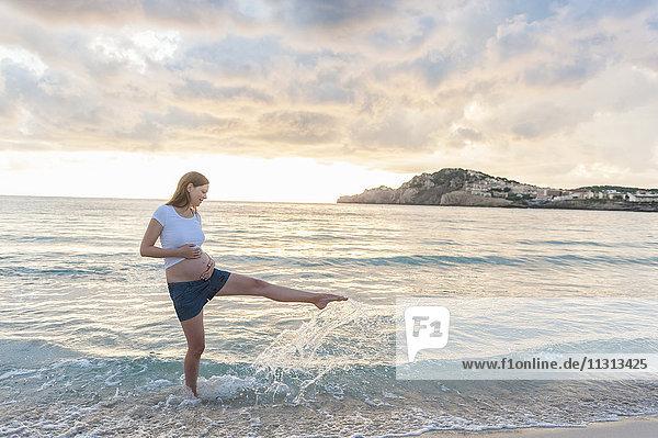 Glückliche schwangere Frau am Strand  die mit Wasser spritzt.