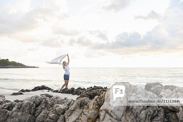 Glückliche schwangere Frau am Strand mit einem Tuch