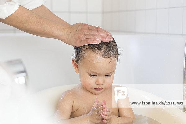 Mutter badet ihr kleines Mädchen in einer Badewanne.