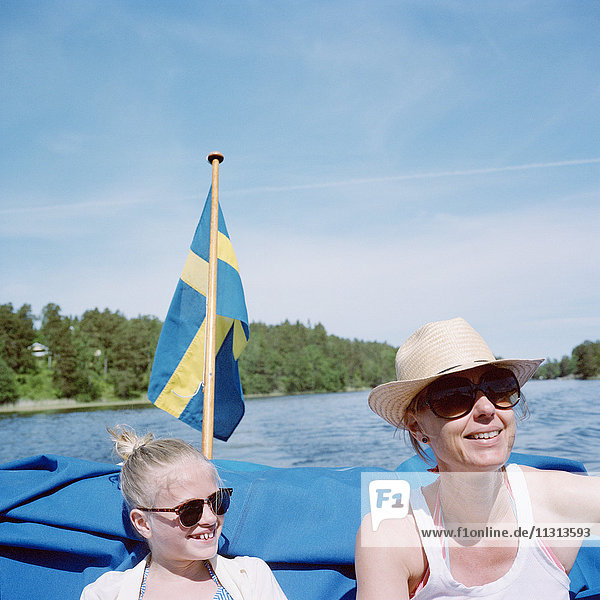 Mother and daughter in boat on lake
