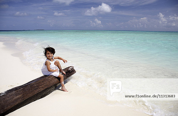 Maldives  girl sitting on a log on a beach