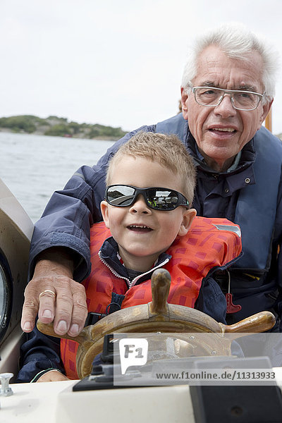 Boy driving boat with grandfather